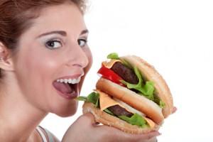Junge Frau mit Hamburger mchte rein beissen