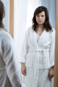 Young sad woman opposite the mirror without self confidence