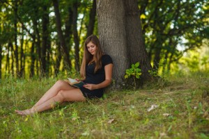 woman girl sits reading a book under a tree in the forest park on the nature of summer in a black dress blond Life style