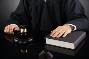 Close-up Of Male Judge With Gavel And Book At Desk